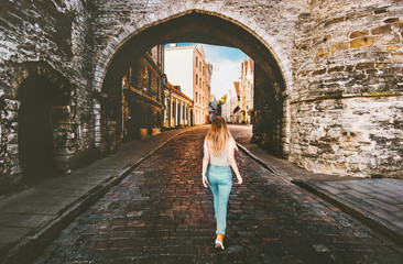Woman tourist walking in Tallinn Old Town  solo traveling vacations in Estonia medieval cobblestone street
