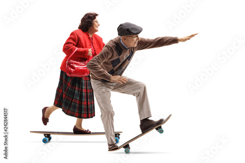 Elderly lady and an elderly man riding a longboard