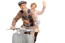 Elderly Man And Woman Riding A Vintage Scooter And Waving