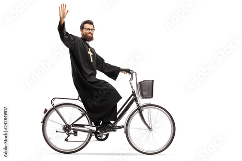 Priest riding a bicycle and waving