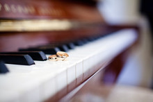 Close-up Of A Pair Of Wedding Rings On The Piano Keys