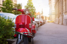 Retro Red Scooter On Street Of The European City. Summer Sun Light In Background. Copy Space Beside.