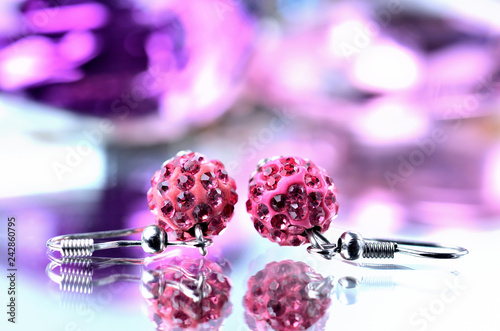 Fotografie, Obraz  Red earrings with red diamonds jewels - reflection effect - colored backgrounds
