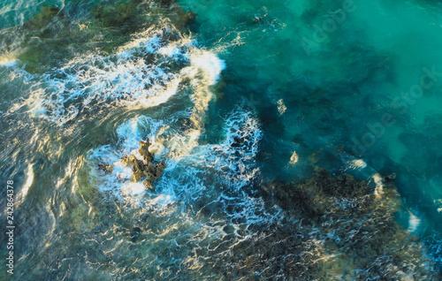 Zdjęcie XXL Widok z lotu ptaka skalistej rafy z fal rozbijających się nad nim w niebiesko zielone i turkusowe wody o zachodzie słońca z długich cieni