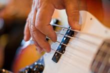 Man's Hand Strumming A Bass Gu...