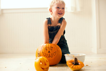 Young Boy Looks Up And Laughs As He Kneels On A Floor And Digs Both Hands Into A Big Pumpkin With A Face Drawn On It With A Bowl And A Finished Small Jack O'Lantern With A Candle Lit Inside In Front Of Him.