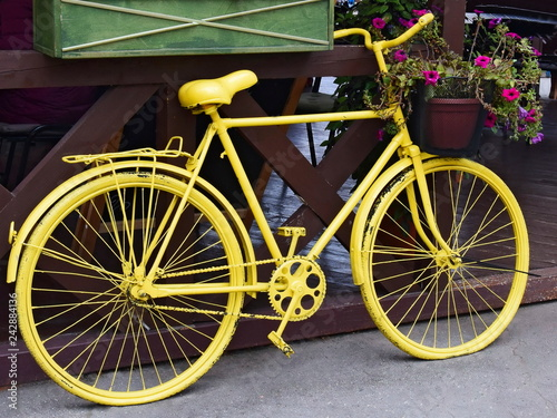 Türaufkleber Fahrrad Yellow bicycle with a basket of flowers outdoors. Retro decor