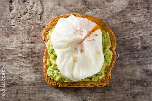 Close up avocado toast with poached egg on wooden table. Top view.