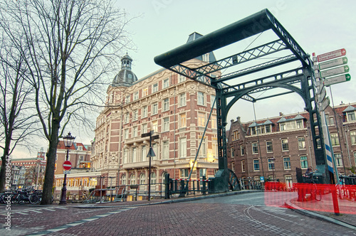 Foto op Canvas Artistiek mon. Staalstraat Bridge, iron lift bridge on Kloveniersburgwal Canal in Amsterdam, Netherlands, early in the morning in winter.