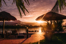 Beautiful Pink Tropical Sunset Silhouette Of Thatch Umbrellas Palm Leaves River Bank And Mountains In The Background