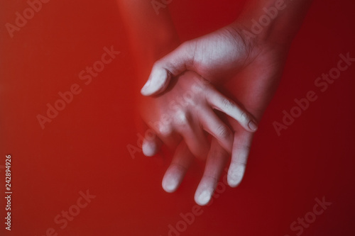 Photo plexus of the hands of a man and a woman drowning in red water similar to blood,