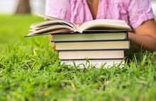 Woman Reading An Open Book On The Grass With Pile Of Books On The  Background.
