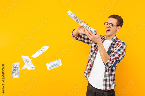 Fotomural happy man, wearing glasses and a plaid shirt, throwing out money banknotes on a