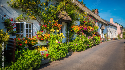 Foto Cute old English house with a thatched roof and flowers in a green hilly landscape on a summer sunny day with blue sky in the UK in a holiday Dorset countryside between Sidmouth and Lyme Regis