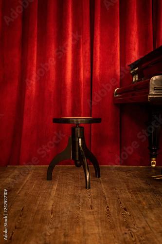 Plakat Fortepianowa ławka na scenie na czerwonym zasłony tle.
