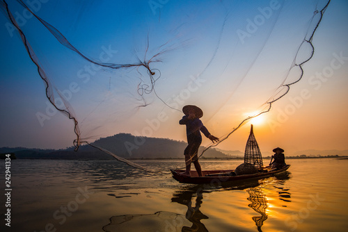 Canvas-taulu Fisherman on boat river sunset Asia fisherman net using on wooden boat casting n