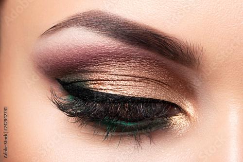 Obraz na płótnie Close up of beautiful woman eye with multicolored smokey eyes makeup