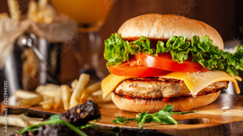 Fototapeta American cuisine concept. Juicy burger with meat patty, tomatoes, cheddar cheese, lettuce and homemade bun. In the background are french fries and a glass of beer. Close up obraz