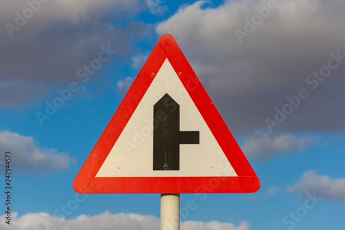 Fotografía  Fork in the road roadsign with a blue sky and cloudy background.
