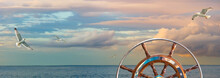 Marine Sunrise With Cloudy Sky In Pastel Colors And Flying Seagulls Over The Ocean. Calm Seascape With A Skippers Wheel On A Ship For Your Concept Of Sea Voyage Or Nautical Expedition.