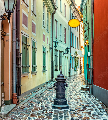 Winter in narrow medieval street of old Riga - the capital and largest city of Latvia, a major commercial, cultural, historical and tourist center of the Baltic region