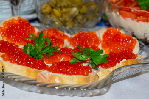 Foto op Canvas Buffet, Bar Red caviar and parsley sandwiches on New Year's table