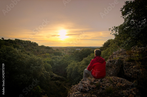 Fantastique Paysage man looking at sunset in a mountain with red jacket