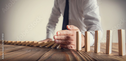 Fotografía Chain Reaction In Business Concept, Businessman Intervening Dominoes Toppling