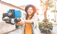 Happy Asian Woman Vlogging With Gimbal Tripod And Smartphone