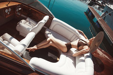 A Beautiful Girl, A Model In A Swimsuit And A Wide-brimmed Hat Lies On The Deck Of A Luxurious Wooden Speed Boat On The Background Of The Sea In Summer.