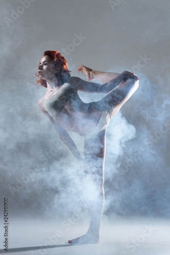 Dancing in cloud concept. Muscle redhead beauty female girl adult woman dancer athlete gymnast in dust fog smoke wearing dance clothing making dance element performance on isolated grey background
