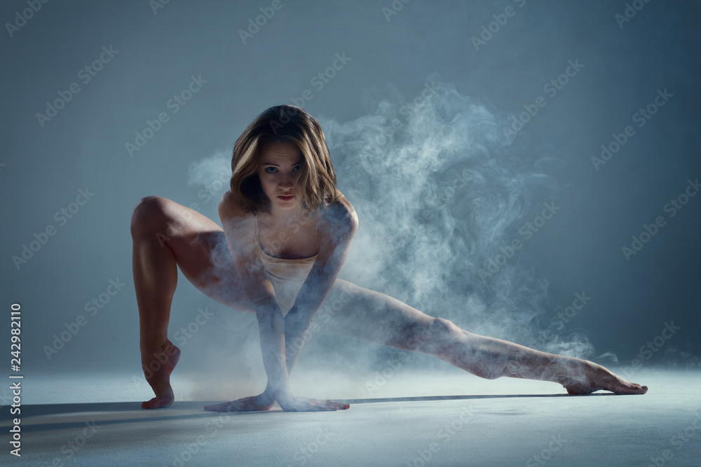 Fototapeta Dancing in cloud concept. Muscle brunette beauty female girl adult woman dancer athlete in fog smoke fume wearing dance bodysuit making sexy dance element performance on isolated grey background