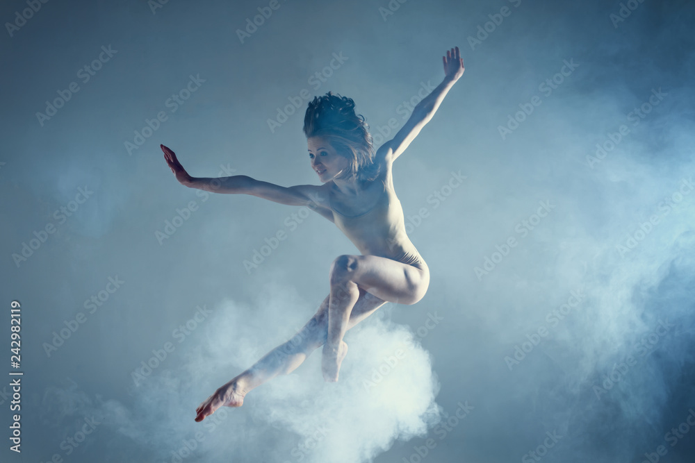 Fototapeta Dancing in cloud concept. Muscle brunette beauty female girl adult woman dancer athlete in dust / fog. Girl wearing dance bodysuit jumping in mid air, performance on isolated grey / black background