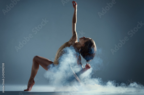 Photo Stands Dance School Dancing in cloud concept. Muscle brunette beauty female girl adult woman dancer athlete in fog smoke fume wearing dance bodysuit making emotional dance element performance on isolated grey background