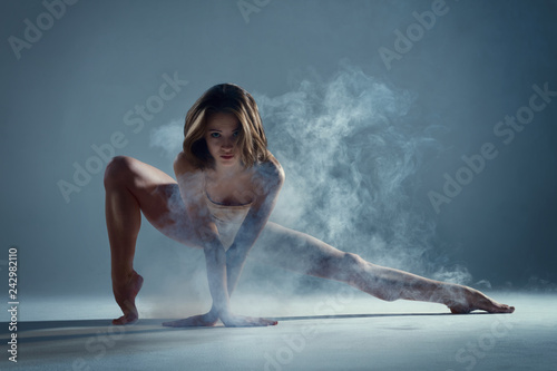 Spoed Foto op Canvas Dance School Dancing in cloud concept. Muscle brunette beauty female girl adult woman dancer athlete in fog smoke fume wearing dance bodysuit making sexy dance element performance on isolated grey background