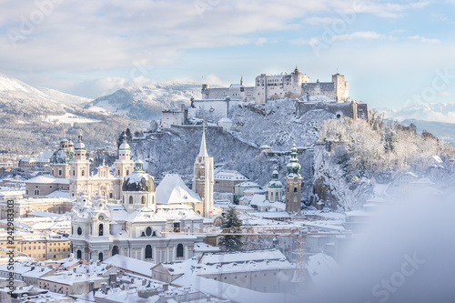 Fototapeta premium Panorama Salzburga zimą: zaśnieżone historyczne centrum, słońce