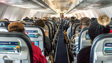 Passengers Seated Inside Of A Commercial Passenger Airplane. Travelers Going Across The Globe.