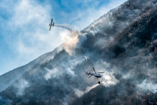 Firefighting Aircraft And Helicopter Dropping The Water For Fighting A Fire On Mountain.