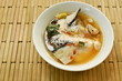 spicy salmon fish head and straw mushroom in Tom Yum soup on bowl