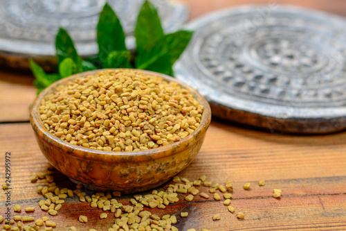 Fototapeta Bowl with fenugreek seeds close up, used for cooking and traditinal medicine, spices collection obraz