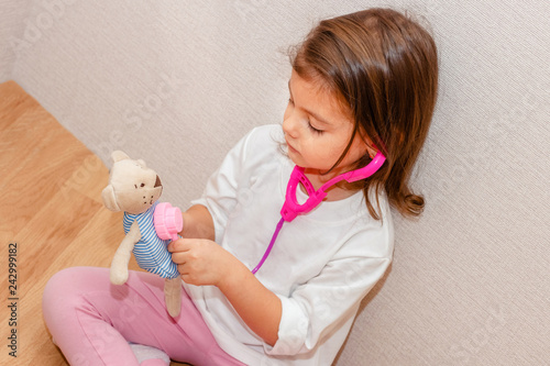Beautiful little girl pretending to be a nurse or doctor and auscultate her tedd Canvas Print