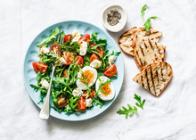 Breakfast Salad - Arugula, Cherry Tomatoes, Mozzarella And Boiled Egg With Olive Oil, Mustard, Lemon Dressing On A Light Background, Top View