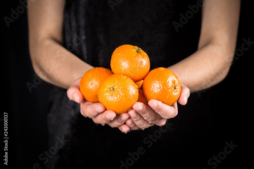 Wet orange tangerines in woman hands on black background