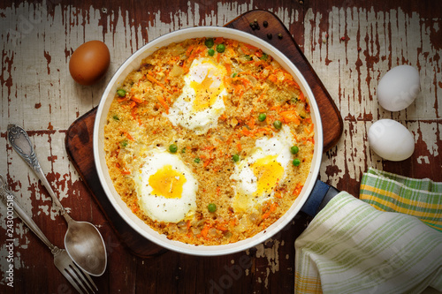 Valokuva  Wheat porridge with vegetables and eggs in a white pan