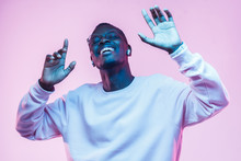 Young African Man Listening To Music With Wireless Earphones And Dancing Isolated On Pink Background