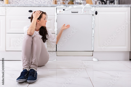 Valokuva  Upset Woman Sitting In Front Of Damaged Dishwasher