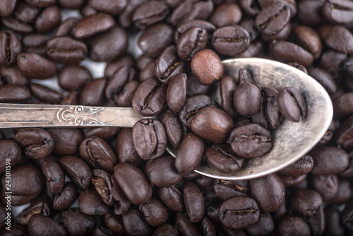 Fotografie, Obraz  Roasted coffee beans in Old silver vintage dessert  spoon on brown  coffee beans background