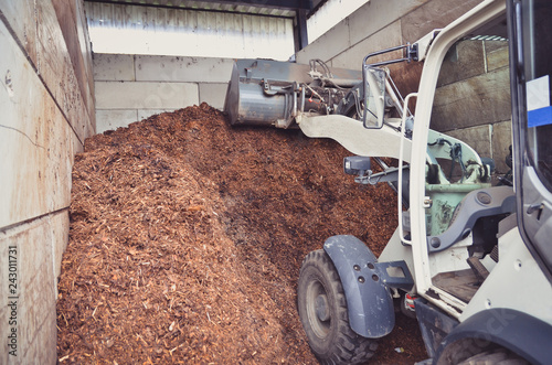 Wheel loader is working with a fertilizer storage as a result of organic wastes recycling process on a biogas plant Wallpaper Mural