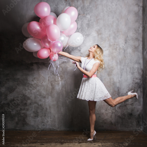 Photo  Charming young blonde in a white dress with pink balloons, fly at the party
