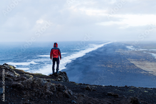 фотография Person standing at Dyrholaey lighthouse in Iceland looking out over the black sa